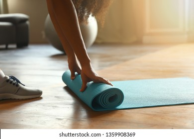 Sporty African-American woman with yoga mat at home