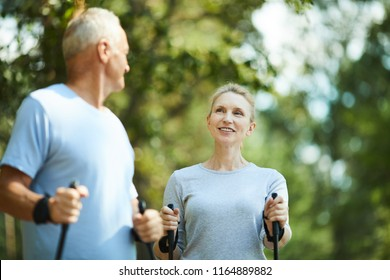 Sporty aged female and her husband trekking in park or forest on summer weekend