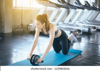 Sporty asian female doing workout and exercise with roller wheel at the gym center
