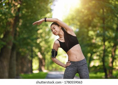Sporty asian girl exercising before jogging at park, stretching her muscles outdoors, feeling healthy and motivated, copy space