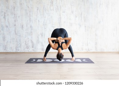 Sporty asian girl standing in yoga asana on mat against concrete wall. Girl leaned over head down with arms behind back in asana, pose, wearing black sportswear. Yoga trainer in yoga studio.