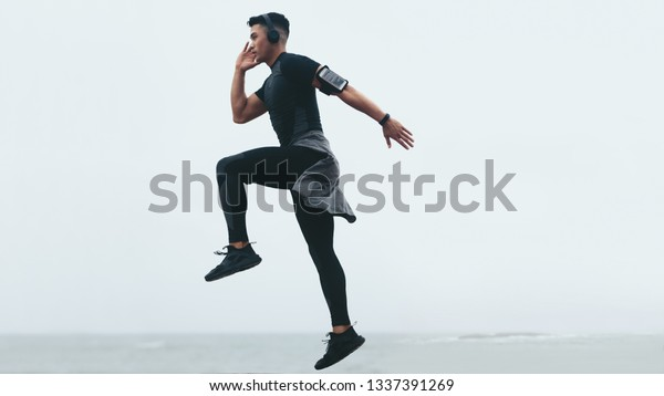 Sporty asian man doing intense exercises. Side view of fitness male exercising jump and lunge.