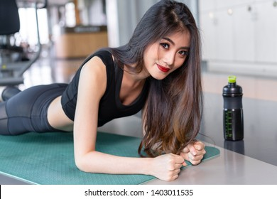 Sporty asian woman exercise doing plank at gym workout fitness, female athlete muscle building strong healthy lifestyle with protein shake bottle.