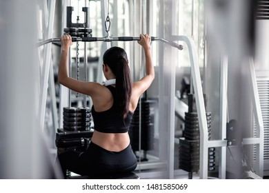 Sporty Asian woman exercising with lat pulldown machine to build arm and shoulder muscle in fitness gym. Bodybuilding and healthy lifestyle concept.