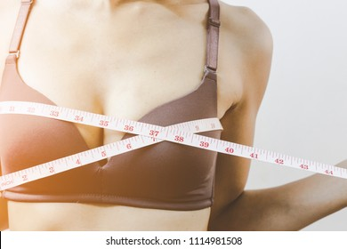 Sporty Asian woman measuring up her chest. happy girl checking her breast measurement. Medical Breast enhancement,Breast Surgery or beautiful fashion concept