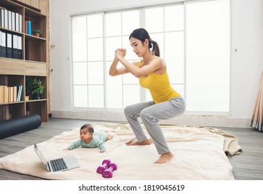 Sporty asian woman in yellow sportswear is exercise on the floor with daughter baby, dumbbells and using a laptop. Young mother and infant make squat pose at home in the living room.