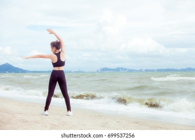 Sporty asian women fitness age 30-40 are warm up muscular body for jogging at the beach in sunrise light . Moments of joy and relaxation in the morning. Customize pastel bright colors tone .