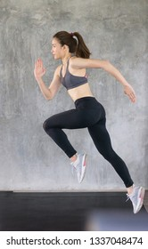 Sporty asian young woman jumping and running on grey background