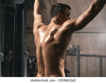 Sporty athletic man doing chin ups for arms and back muscles