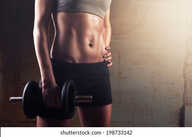 Sporty athletic woman ready for hard training with dumbbells