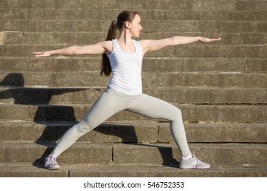 Sporty attractive happy young woman practicing yoga, standing in Warrior Two exercise, Virabhadrasana 2 pose, working out, wearing sportswear, outdoor, stone stair background with a shadow