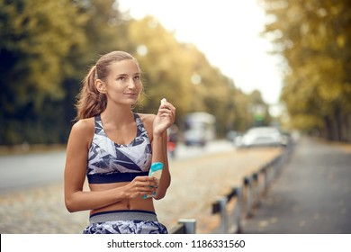 Sporty attractive slender young woman sitting on a roadside rail eating a piece of a protein bar as she takes a break from her daily jog, with copy space