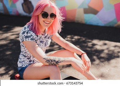Sporty attractive woman with pink hair and healthy smile, with tattoo on hand, sitting on her longoard waiting her friends in the park. Lifestyle and extreme sport concept.