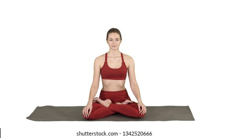 Sporty attractive woman practicing yoga, sitting in Lotus exercise, Siddhasana pose breathing on white background.