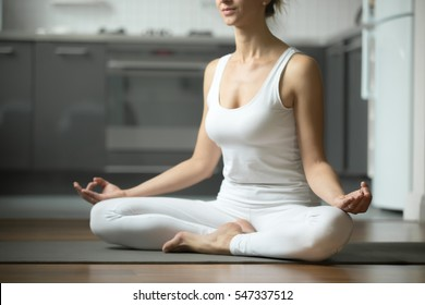 Sporty attractive woman practicing yoga, sitting in Half Lotus exercise, Siddhasana pose, working out, wearing white sportswear, indoor, home interior background. Midsection close up