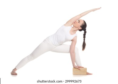 Sporty attractive young beginning yoga woman student in white sportswear doing lunge exercise for spine, utthita parsvakonasana with wooden brick, studio shot, isolated, full length