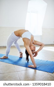 Sporty attractive young brunette woman ddoing yoga exercise for back and hand stretch in a gym with white wall background. Athletic flexible female doing Wild Thing, Flip-the-Dog pose, Camatkarasana