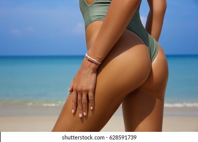 Sporty back of a beautiful woman in bikini on sea background with copyspace. Sexy buttocks