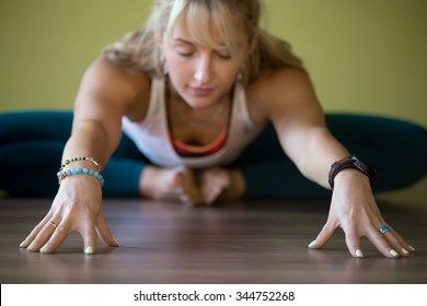 Sporty beautiful blond young woman in sportswear working out indoors, doing Butterfly Pose with closed eyes, sitting in Purna Titli or Baddha Konasana Posture, full length, close-up, focus on hands
