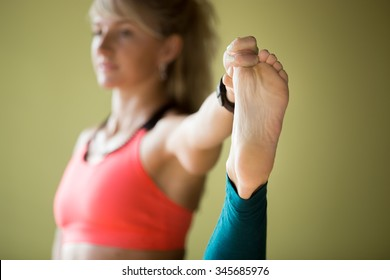 Sporty beautiful blond young woman in sportswear working out indoors, doing Utthita Hasta Padangustasana, Extended Hand To Big Toe yoga posture, close up, focus on foot