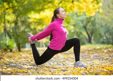 Sporty beautiful happy young woman practicing yoga, standing in Hip Flexor Low Lunge, Anjaneyasana pose, working out outdoor on autumn day wearing sportswear sweatshirt. Full length