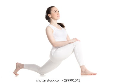 Sporty beautiful smiling young woman doing low lunge exercise, anjaneyasana, ashva sanchalasana (dragon flying high - yin pose), three-quarters view, studio full length shot, isolated