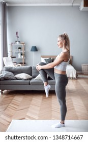 Sporty beautiful woman exercising at home to stay fit. Workout indoors.