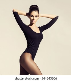 Sporty and beautiful woman in pantyhose and leotard. Fashion model posing concept.