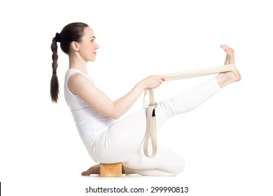 Sporty beautiful young beginning yoga student in white sportswear doing exercises for legs using props: block and strap, sitting in Heron Pose, studio full length isolated shot, side view