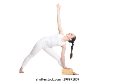 Sporty beautiful young beginning yoga female student standing in Utthita Trikonasana, Extended Triangle Pose with wooden block, studio full length profile view on white background, isolated