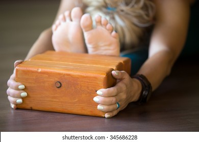 Sporty beautiful young blond woman in sportswear working out indoors, doing exercise for spine, shoulders, hamstrings, sitting in paschimothanasana posture, using wooden bricks, close-up