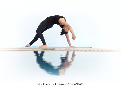 Sporty beautiful young woman in black sportswear performing exercise bridge, asana Camatkarasana, Wild Thing, Dancing Dog yoga pose.Healthy lifestyle in white background with refection
