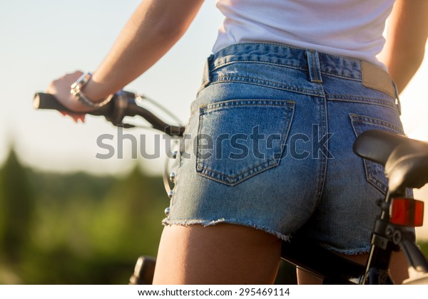 Sporty beautiful young woman butt on bike on summer day, close up, back view
