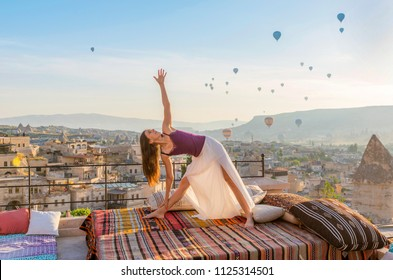 Sporty beautiful young woman practicing yoga, standing in Utthita Trikonasana posture, Extended Triangle pose. In Cappadocia Turkey in the morning with balloons on background