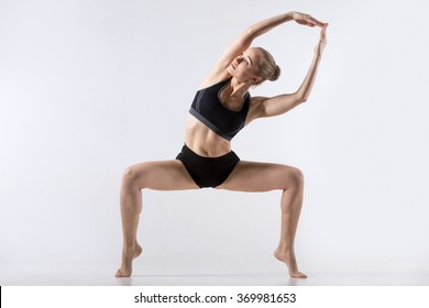 Sporty beautiful young woman practicing yoga, doing side bend variation of Goddess, Temple or Sumo Squat Pose, working out wearing black sportswear, studio full length, grey background