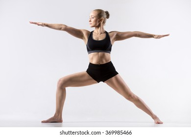 Sporty beautiful young woman practicing yoga, standing in Warrior II posture, Virabhadrasana Two pose, working out wearing black sportswear, studio full length, grey background