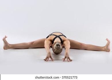 Sporty beautiful young woman practicing yoga, doing Upavishtha Konasana, Wide-Angle Seated Forward Bend, Straddle (dragonfly) yin yoga posture, working out wearing black sportswear, studio