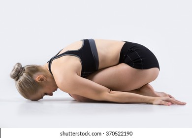 Sporty beautiful young woman practicing yoga, doing Balasana, Child Pose, restorative exercise for stress relief, working out wearing black sportswear, studio, full length