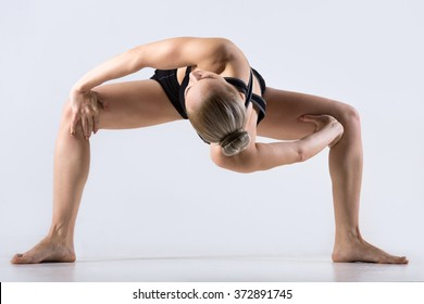 Sporty beautiful young woman practicing yoga, twisting in variation of Goddess, Temple or Sumo Squat Pose, working out wearing black sportswear, studio full length, grey background