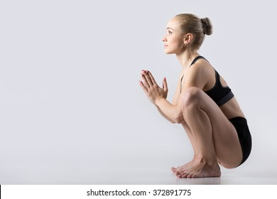 Sporty beautiful young woman practicing yoga, sitting in squat, Garland Pose, Malasana, stretching back muscles, hips, ankles, working out wearing black sportswear, studio