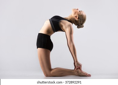 Sporty beautiful young woman practicing yoga, doing Ushtrasana, Camel Pose, working out wearing black sportswear, studio, full length