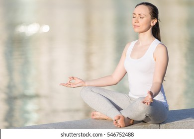 Sporty beautiful young woman practicing yoga, sitting in Easy Seat exercise, Sukhasana pose, working out, enjoying meditation session. Outdoor full length, water surface background. Copy space