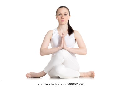 Sporty beautiful young woman sitting in Gomukhasana, Cowface pose (yin yoga Shoelace posture), asana for stretching hips and thighs, studio full length shot on white background, front view, isolated