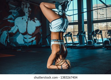 Sporty beautiful young woman in white sportswear doing Supported headstand exercise, salamba sirsasana 1, studio full length isolated shot, side view. yoga in gym.