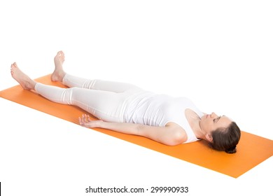 Sporty beautiful young woman in white sportswear lying with closed eyes on orange mat in Shavasana (Savasana, Corpse Pose), studio shot, isolated, full length three-quarters view