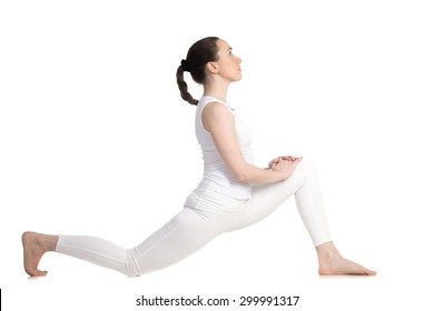 Sporty beautiful young woman in white sportswear doing low lunge exercise, anjaneyasana, ashva sanchalasana (dragon flying high - yin pose), profile view, studio full length shot, isolated