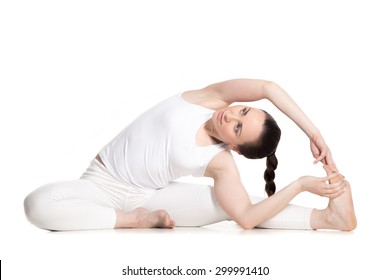 Sporty beautiful young woman in white sportswear sitting in Revolved Head to Knee pose, doing parivritta Janu Sirsasana, studio full length isolated shot