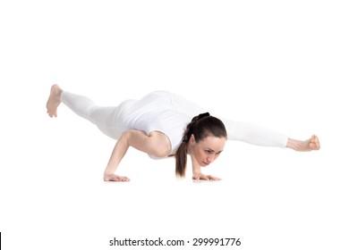 Sporty beautiful young woman in white sportswear standing in Eka Pada Koundinyasana 2, twisted one legged arm balance, studio full length isolated shot, front view