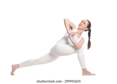 Sporty beautiful young woman in white sportswear doing lunge exercise for spine, standing in variation of Revolved Side Angle Pose with hands in prayer gesture, full length isolated studio shot