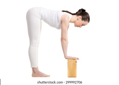 Sporty beautiful young woman in white sportswear doing variation of Standing Half Forward Bend, Ardha Uttanasana pose with wooden blocks, studio full length shot on white background, isolated